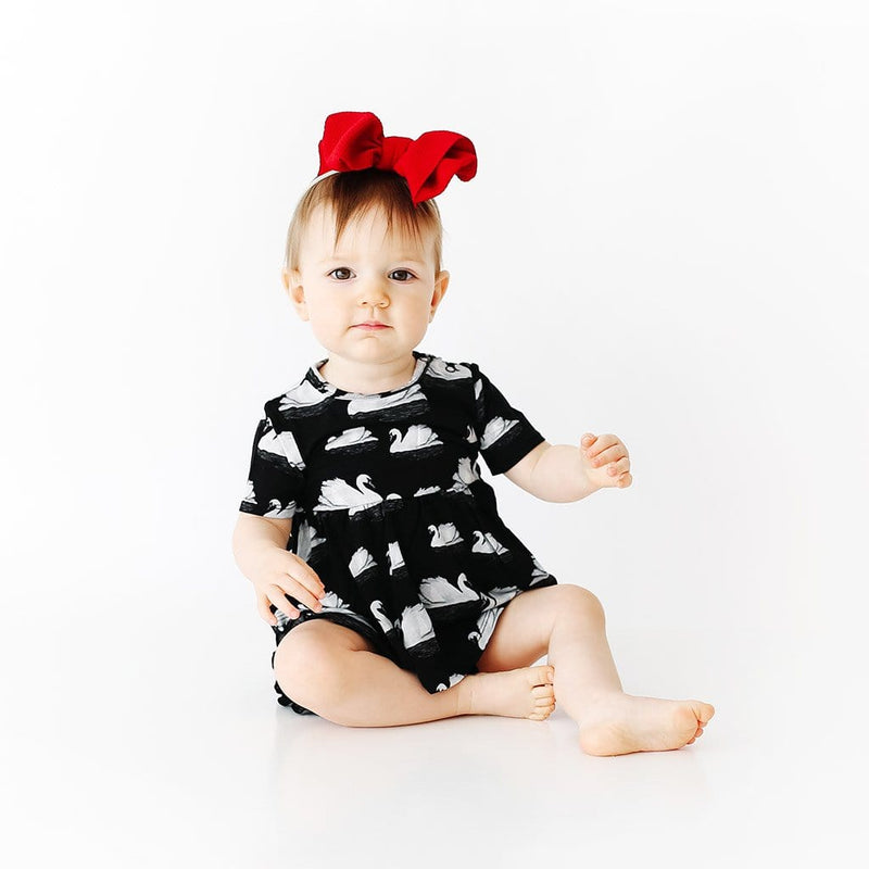Baby sitting wearing Leia Short Sleeve Peplum Ruffled Bummie Set with swan pattern