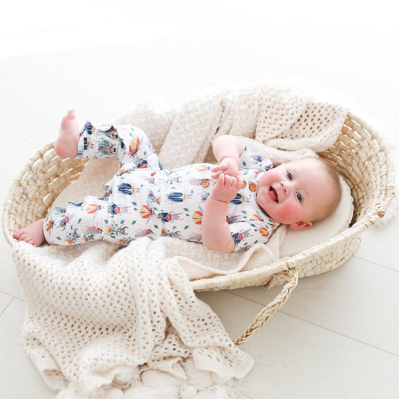 Baby on crib wearing lennox short sleeve henley romper