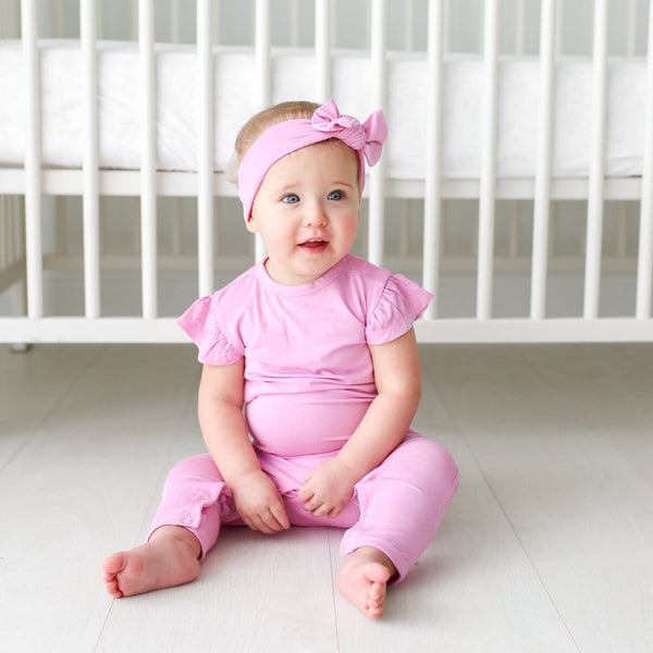 Baby wearing lilac ruffled cap sleeve romper