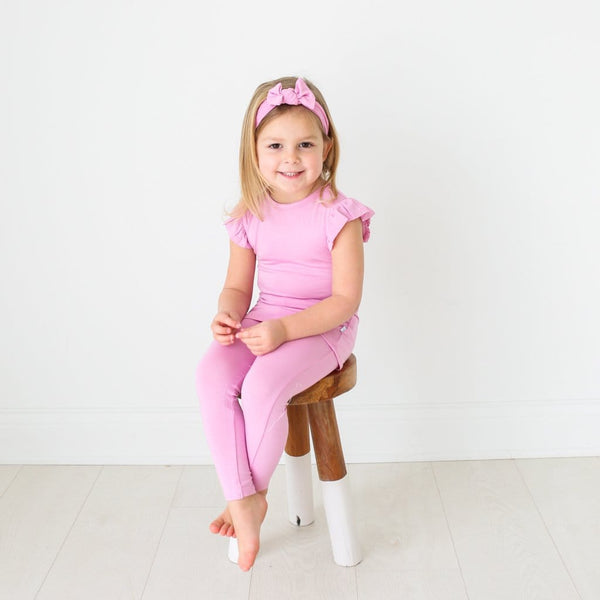 Toddler wearing lilac ruffled cap sleeve pajamas