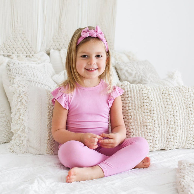 Toddler sitting wearing lilac ruffled cap sleeve pajamas
