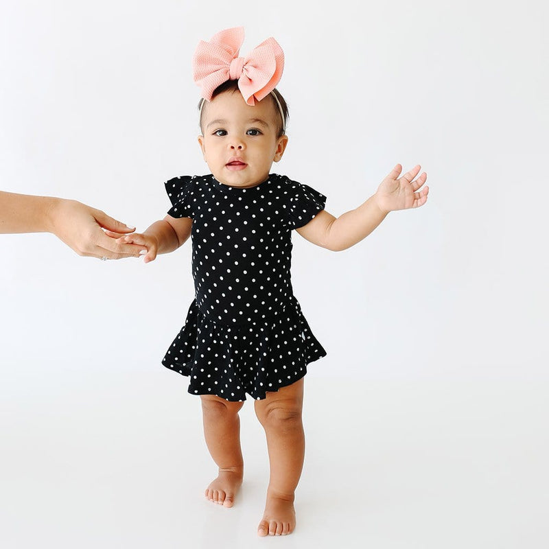 Baby wearing Lilly Ruffled Cap Sleeve Twirl Skirt Bodysuit with polka dots pattern