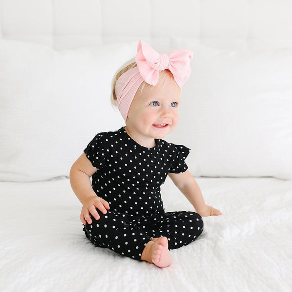 Baby sitting wearing Lilly Ruffled Cap Sleeve Romper with polka dots pattern