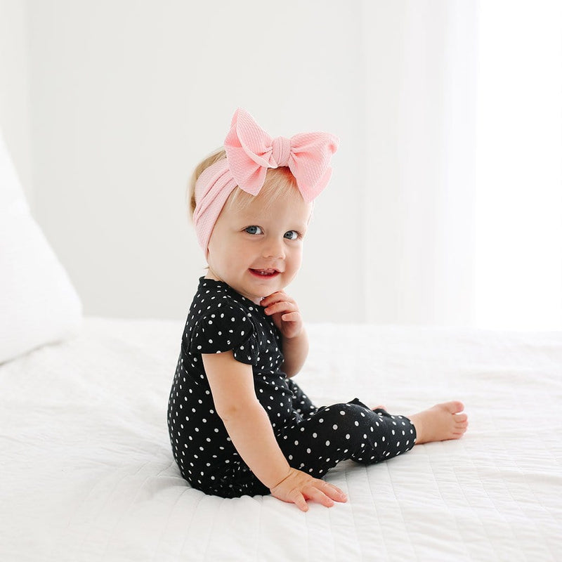 Baby sitting on bed wearing Lilly Ruffled Cap Sleeve Romper with polka dots pattern