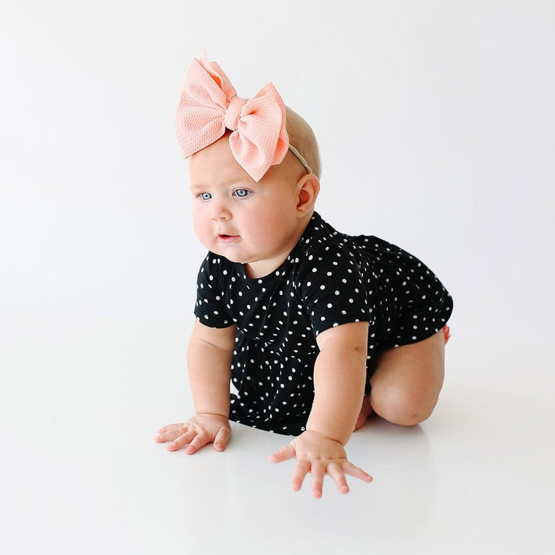 Crawling baby wearing Lilly Short Sleeve Peplum Ruffled Bummie Set with polka dots pattern