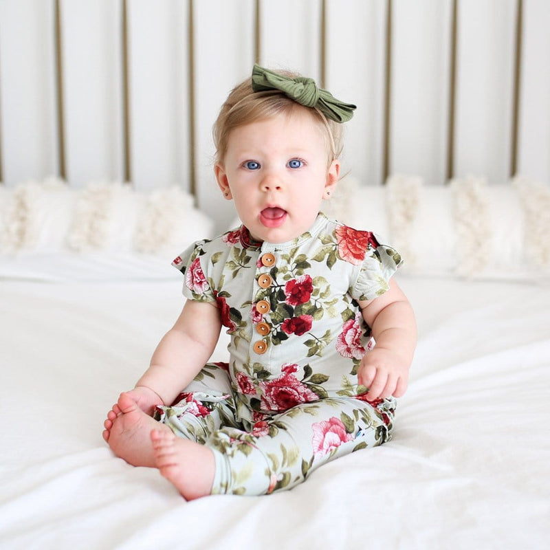 Sitting baby on Lizzie ruffled cap sleeve henley romper