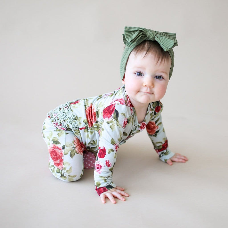 Baby crawling wearing Lizzie footie ruffled zippered one piece