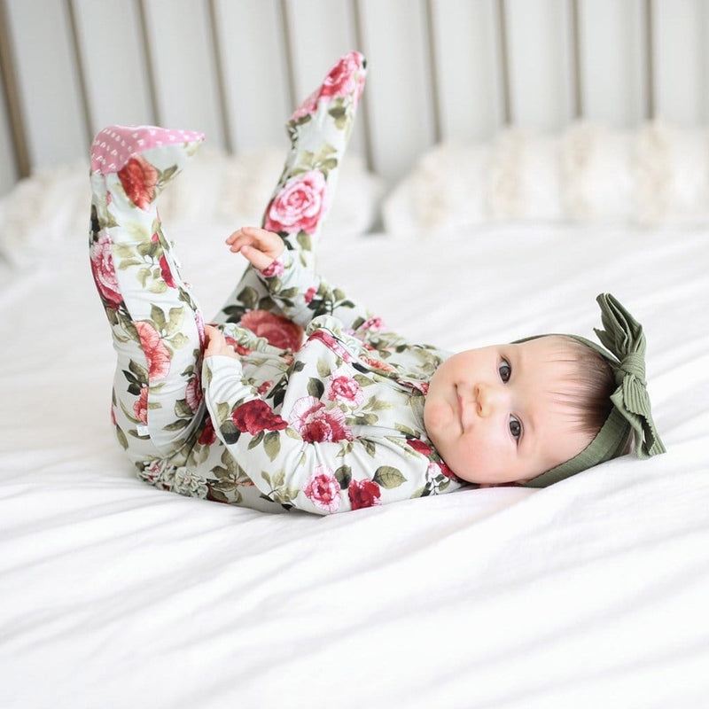 Baby lying on bed wearing Lizzie footie ruffled zippered one piece