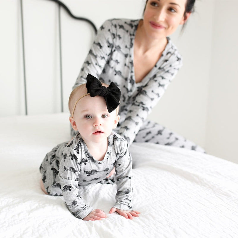 Baby on bed wearing Logan Long Sleeve Twirl Skirt Bodysuit