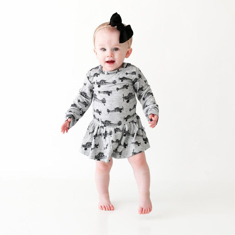 Baby standing wearing Logan Long Sleeve Twirl Skirt Bodysuit