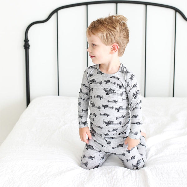 Toddler on bed wearing Logan Long Sleeve Pajamas