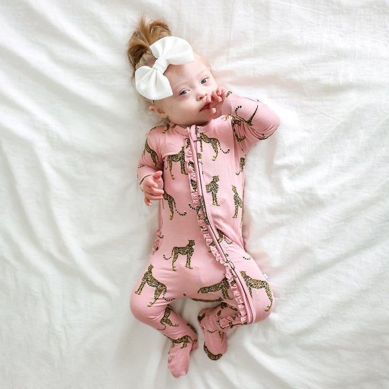 Baby on bed wearing Mara footie Ruffled zippered one piece