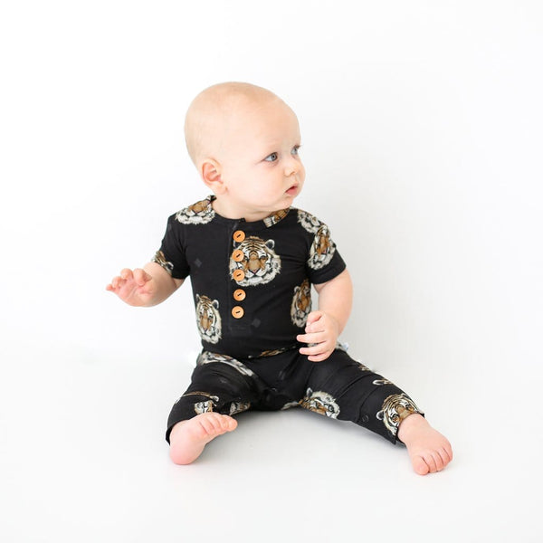 Baby sitting on Mateo short sleeve henley romper