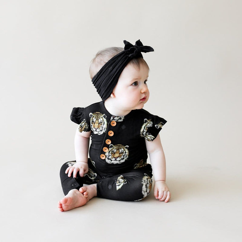 Baby sitting on Mateo ruffled cap sleeve henley romper