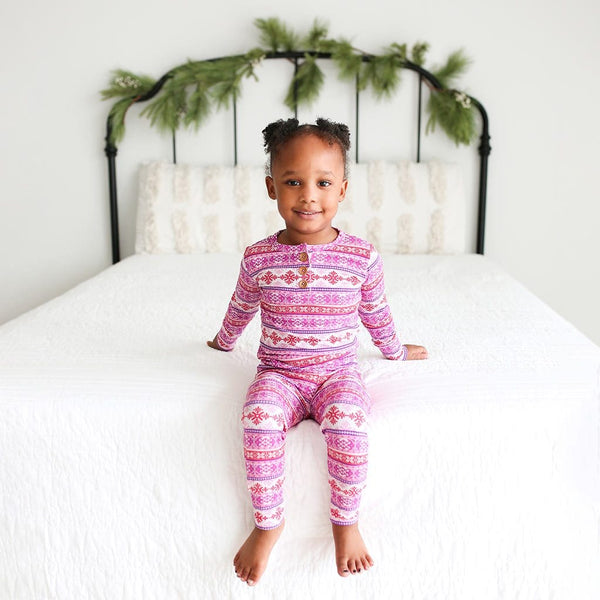 Toddler sitting on bed wearing Maya Long Sleeve Henley Pajamas in purple and red print