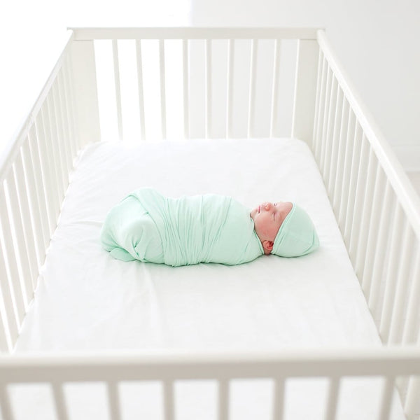 Baby wearing mint swaddle beanie set
