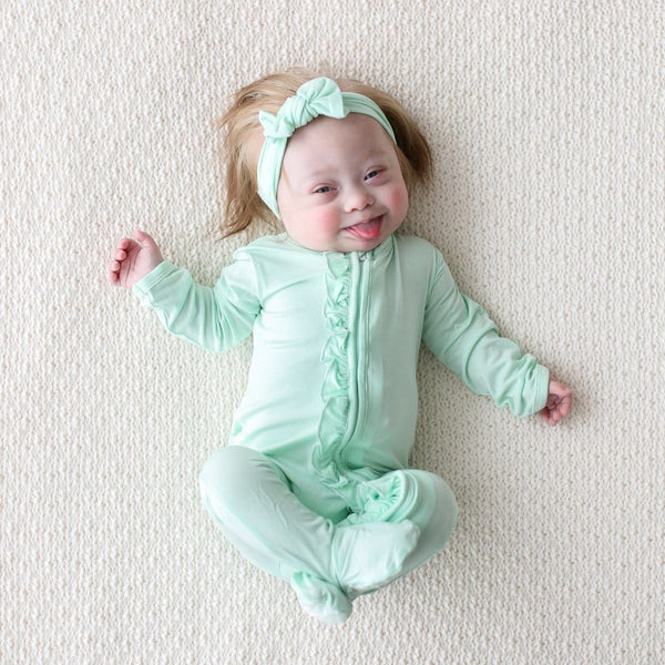 Baby wearing mint footie ruffled zippered one piece