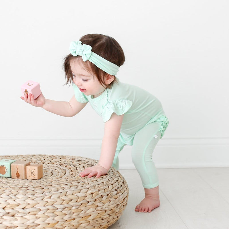 Toddler playing wearing mint ruffled cap sleeve romper