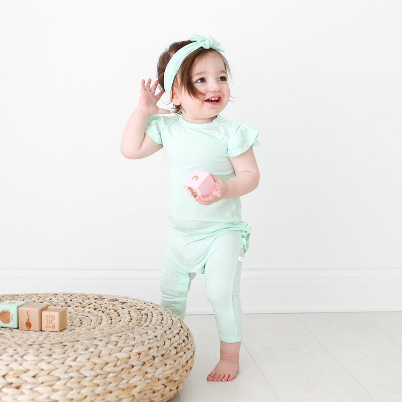 Toddler wearing mint ruffled cap sleeve romper