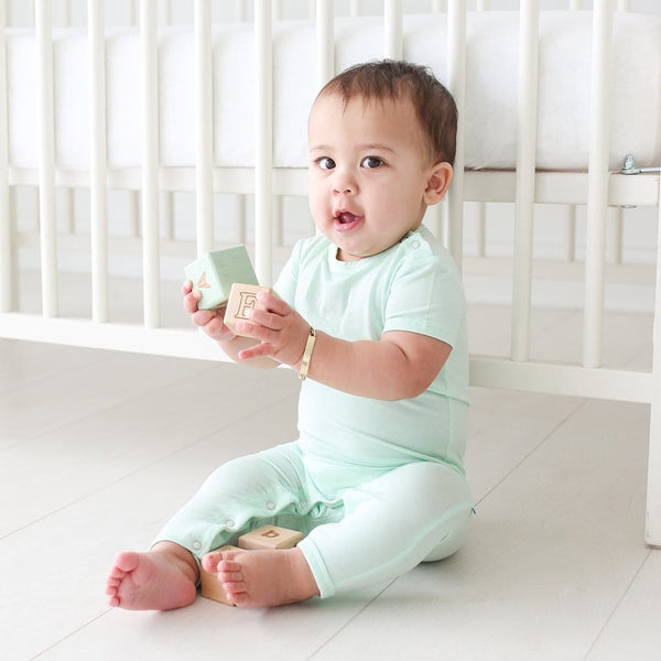 Baby sitting wearing mint short sleeve romper