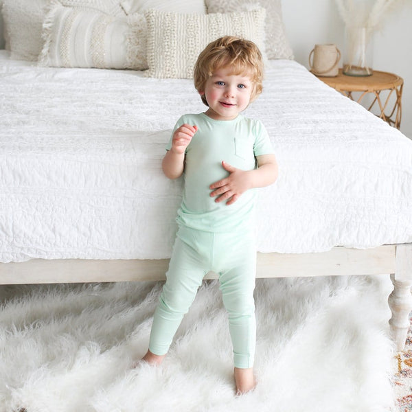 Toddler wearing mint short sleeve pajamas