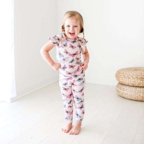 Toddler girl wearing Nora ruffled cap sleeve pajamas