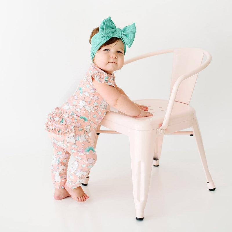 Standing baby wearing pink Olive Ruffled Cap Sleeve Romper with unicorn pattern