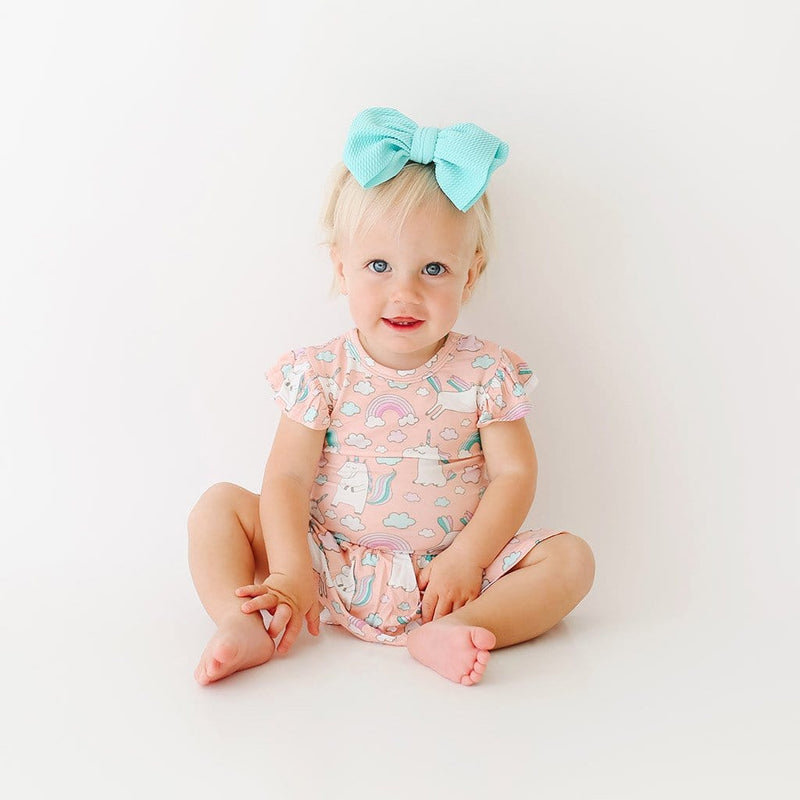 Toddler wearing pink Olive Ruffled Cap Sleeve Twirl Skirt Bodysuit with unicorn pattern