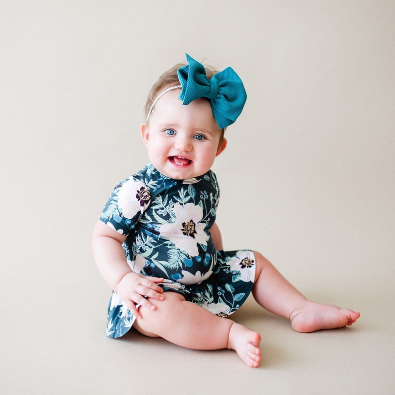 Baby sitting wearing Payton short sleeve twirl skirt bodysuit