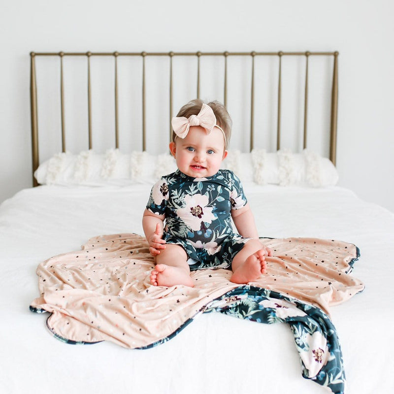 Baby on bed wearing Payton short sleeve twirl skirt bodysuit