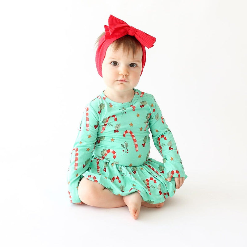 Sitting baby wearing Peppermint Long Sleeve Twirl Skirt Bodysuit with Candy Cane Print