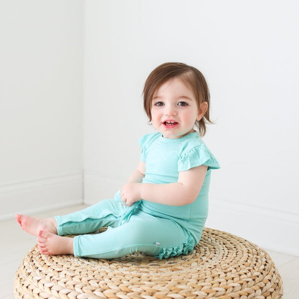 Toddler wearing pool blue ruffled cap sleeve romper