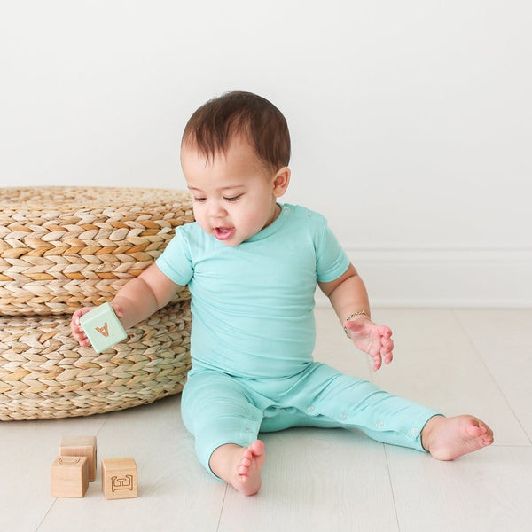 Baby sitting wearing pool blue short sleeve romper