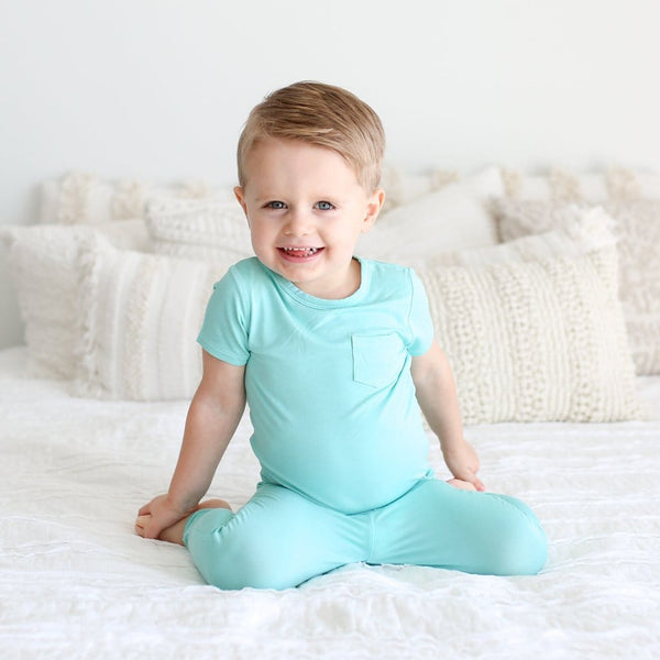 Toddler seating wearing pool blue short sleeve pajamas