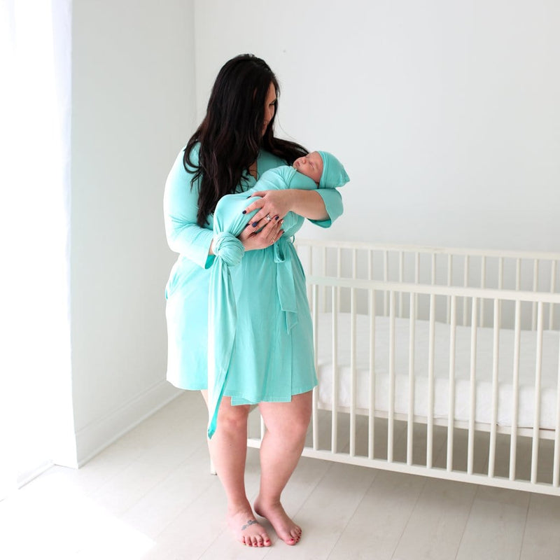 Mommy carrying baby wearing pool blue robe