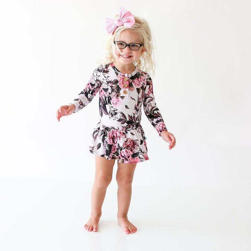 Smiling girl wearing Rima Pink Floral Long Sleeve Henley Twirl Skirt Bodysuit
