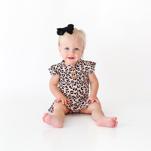 Baby wearing Samara Ruffled Cap Sleeve Henley Twirl Skirt Bodysuit with jaguar pattern