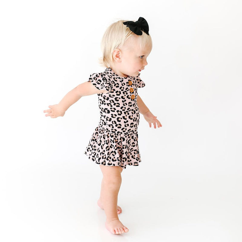 Standing baby wearing Samara Ruffled Cap Sleeve Henley Twirl Skirt Bodysuit with jaguar pattern