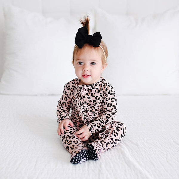 Baby sitting wearing Samara Footie Ruffled Zippered One Piece with jaguar pattern