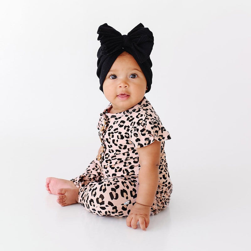 Sitting baby wearing Samara Ruffled Cap Sleeve Henley Romper with jaguar pattern