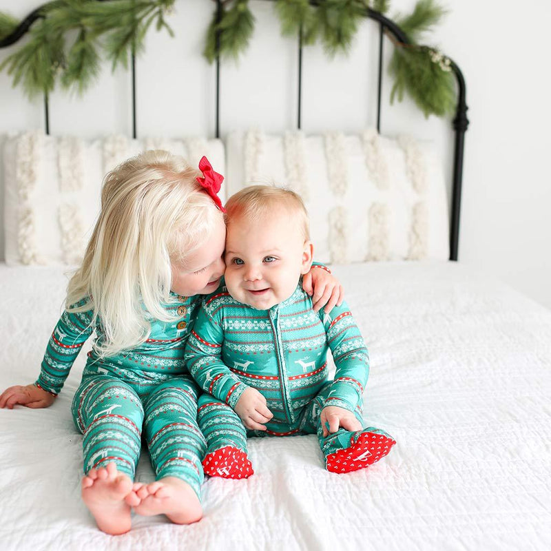 Toddler kissing her sister on Sebastian Footie Zippered One Piece in blue and red print