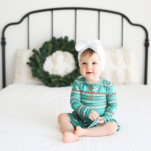 Baby sitting on bed wearing Sebastian Long Sleeve Henley Twirl Skirt Bodysuit