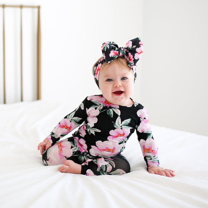 Baby sitting on bed wearing Tenni Long Sleeve Ruffled Romper