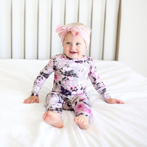 Baby on bed wearing Tessa Long Sleeve Ruffled Romper
