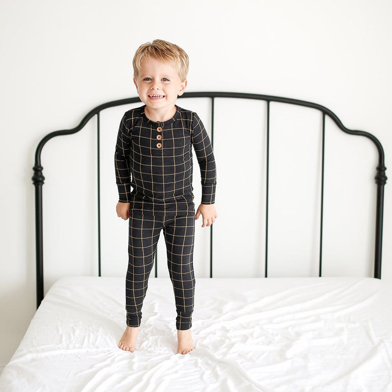 Toddler on bed wearing Tucker Long Sleeve Henley Pajamas