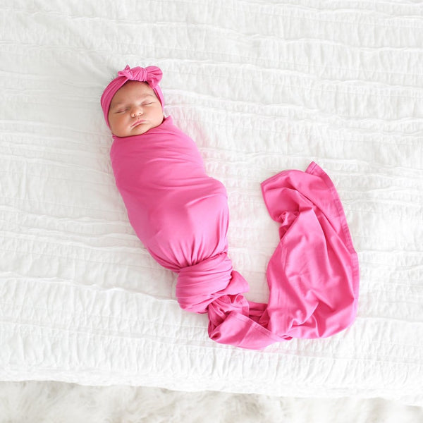 Baby wearing very berry swaddle headband set