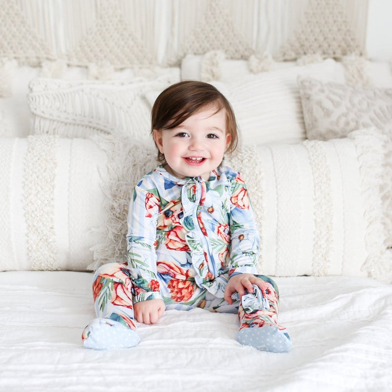 Baby sitting wearing Victoria footie ruffled zippered one piece