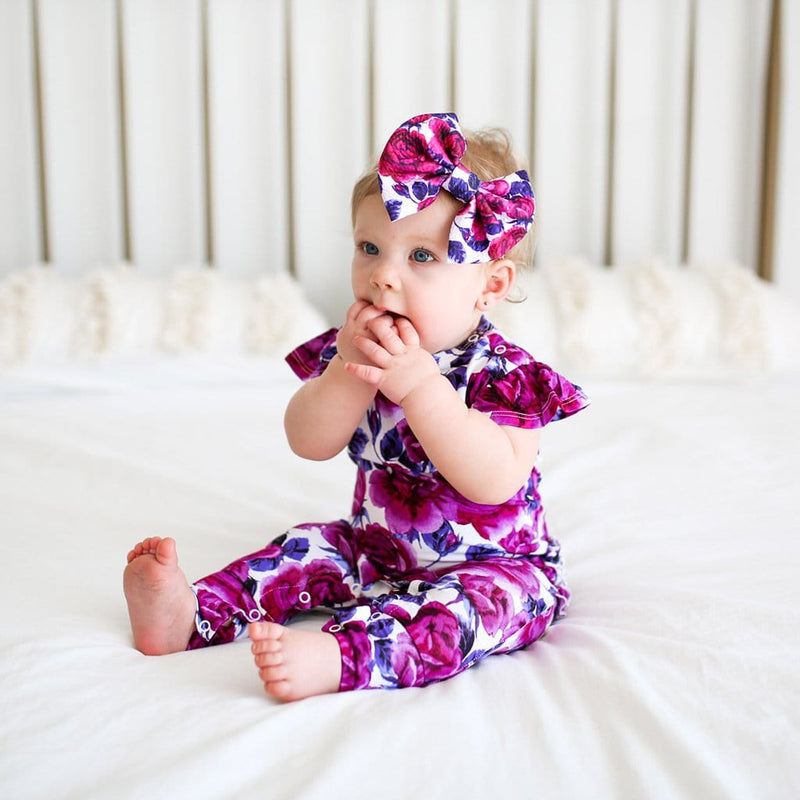 Baby sitting wearing Violet ruffled cap sleeve romper