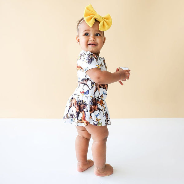 Baby in yellow ribbon wearing Claire Short Sleeve Henley Twirl Skirt Bodysuit in animal print