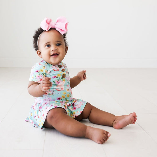 Baby in pink ribbon wearing Missy Short Sleeve Henley Twirl Skirt Bodysuit
